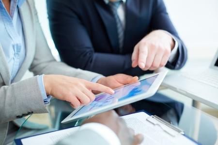 crecimiento personal: Imagen de las manos del hombre durante la discusión del documento de negocios en la pantalla táctil a satisfacer