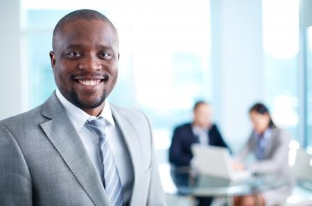 사업: 아프리카 계 미국인 비즈니스 리더의 이미지 작업 환경에서 카메라를보고 스톡 콘텐츠