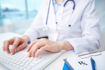 diagnosing: Modern medical person inputting diagnosis into an online data base