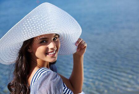 perfil de mujer rostro: Mujer bonita riendo y sosteniendo el ala del sombrero mientras se está sentado en el sol Foto de archivo