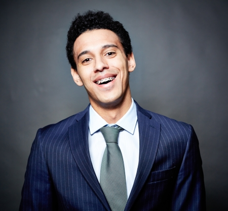 Portrait of a cheerful business guy with braces, against black background photo