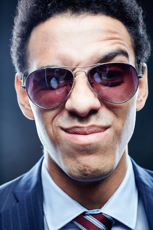 Vertical close-up portrait of a funny business guy making faces photo