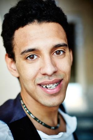 dentalcare: Vertical portrait of an ethnic guy wearing dental braces
