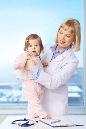 Vertical portrait of a lovely pediatrician holding baby and looking at her photo