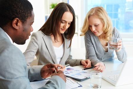 revisando documentos: Reunión del equipo de negocios para analizar el informe financiero