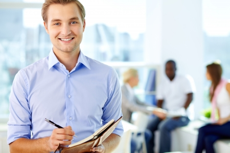 student writing: Portrait of a business guy writing in his organizer Stock Photo