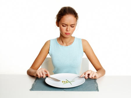 anorexia: Unhappy young woman dieting with peas and leeks, isolated against white