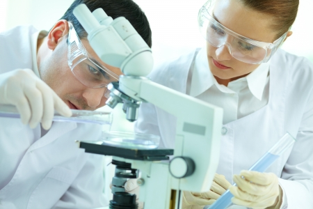 protective spectacles: Concentrated lab workers performing an experiment