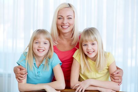 Portrait of a lovely mother embracing her twin daughters photo