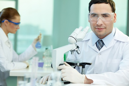 scientific equipment: Portrait of an experienced scientist studying the results of the experiment under the microscope