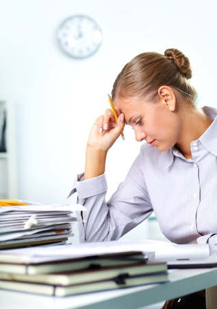 unhappy worker: Vertical shot of a tired businesswoman having a lot of paperwork