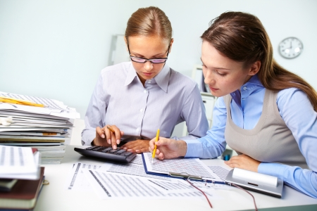 BUSY OFFICE: Concentrated business women reviewing accounting report Stock Photo