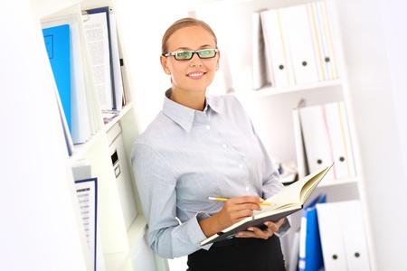 bookkeeper: Retrato de una situaci�n contable sonriendo por las estanter�as Foto de archivo