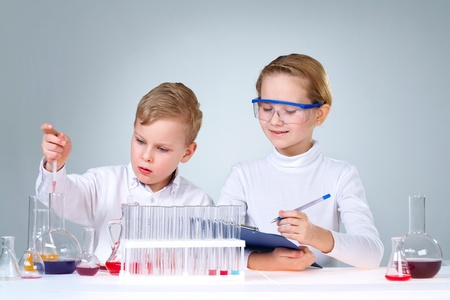 experimenting: Enthusiastic boy and girl experimenting and writing down the results Stock Photo