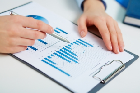 analyzed: Close-up of printed statistics analyzed by a female business worker