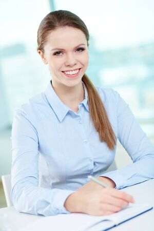 Vertical portrait of a professional business worker being at her workplace photo
