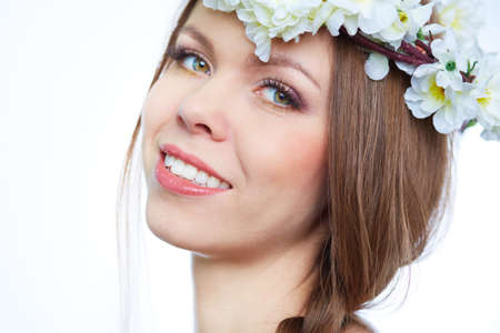 Close-up portrait of a fresh girl wearing flowers in her hair photo