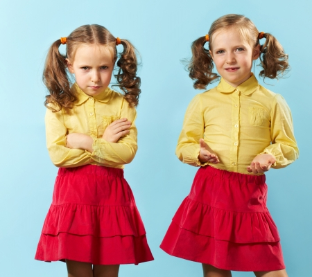positive feelings: Portrait of twin girls with opposite emotions