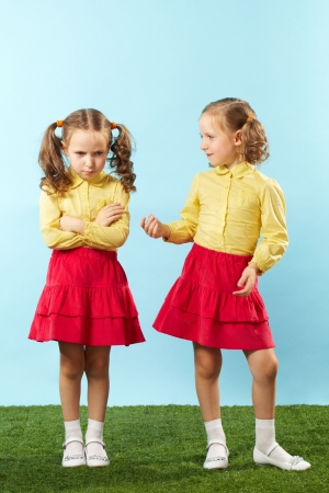 cross armed: Lovely twin trying to cheer up her frowning sister Stock Photo