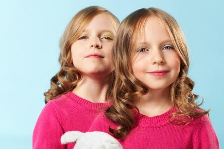 niñas gemelas: Retrato de mujeres jóvenes que disfrutan de su maquillaje y peinado