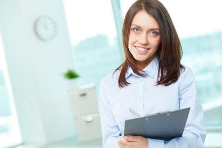 Copy-spaced portrait of a lovely business intern holding clipboard photo