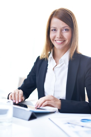 Portrait of smart businesswoman looking at camera during work photo
