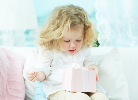 unwrapping: Close-up of a cute girl unwrapping her birthday present