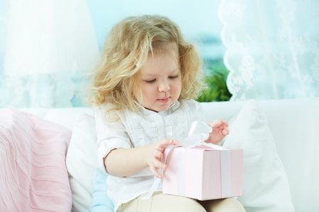 unwrapping: Adorable child unwrapping a birthday gift at home