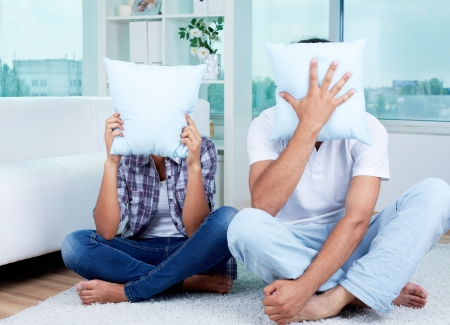 unrecognized: Image of guy and girl sitting on the floor and hiding their faces behind pillows Stock Photo