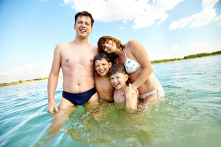 standing water: Photo of happy family standing in water and looking at camera Stock Photo
