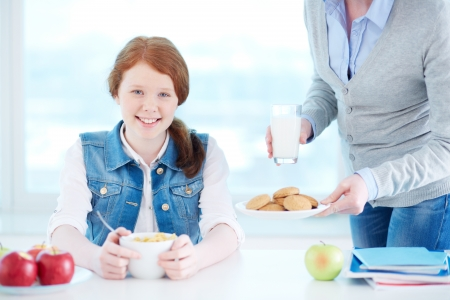 Lovely girl looking at camera while her mother near by offering her some snack Stock Photo - 19142106