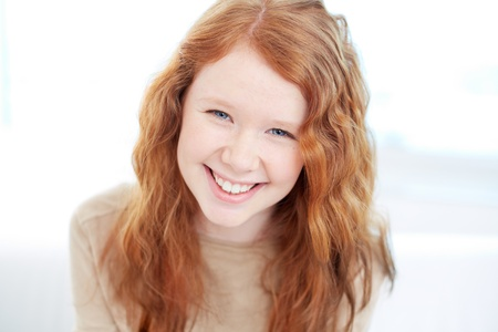 smile close up: Teenage girl with wavy ginger hair looking at camera with smile
