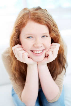 Teenage girl with wavy ginger hair looking at camera with smile photo