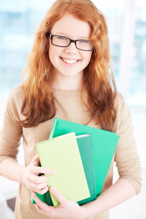 Teenage girl in eyeglasses holding books and looking at camera with smile Stock Photo - 19142101