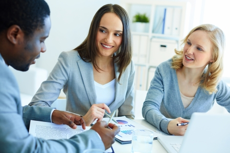 workplace: Image of three business partners discussing documents at meeting