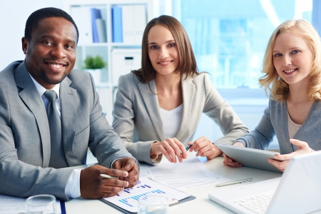 competitive business: Image of three business partners looking at camera with smiles in office Stock Photo