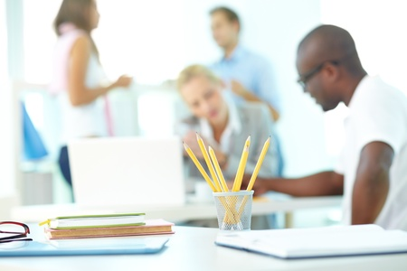 Close-up of several pencils in plastic glass on background of group of students working photo