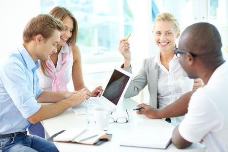 man at work: Group of friendly businesspeople having meeting