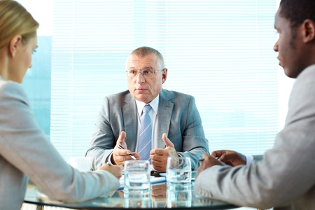 Portrait of serious boss interacting with his employees Stock Photo - 19096333