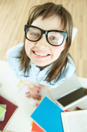 Vertical portrait of a funny school girl wearing nerdy eyeglasses photo
