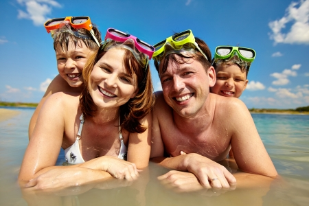scuba goggles:  happy family of divers looking at camera during summer vacation