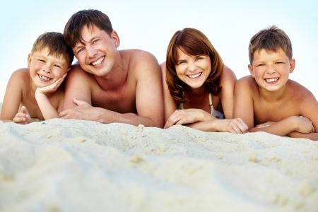 happy family lying on beach and sunbathing on summer vacation photo