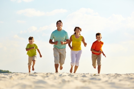 energetic people: Photo of happy family running down the beach on summer Stock Photo
