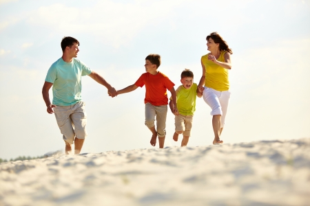 Photo of happy family running down the beach on summer photo