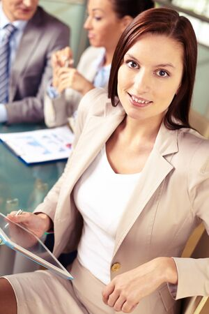 Portrait of friendly specialist with touchpad looking at camera on background of working colleagues photo