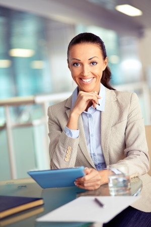 Portrait of confident employee with touchpad looking at camera photo