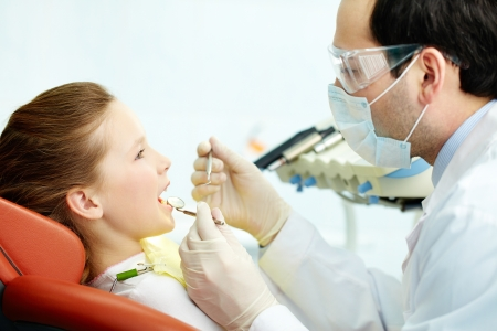 a dentist: Side view of a dentist and his patient