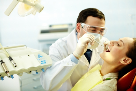 Young woman sitting in dentist's chair while doctor examining her teeth photo