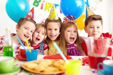 Groupe d'enfants adorables regardant la caméra à la fête d'anniversaire