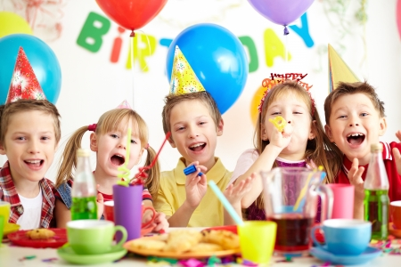 kid friendly: Group of adorable kids having fun by festive table at birthday party